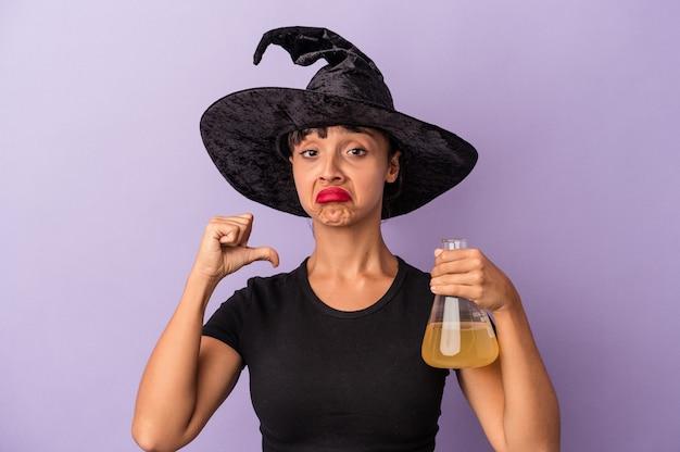 La giovane donna di razza mista travestita da strega che tiene pozione isolata su sfondo viola si sente orgogliosa e sicura di sé, esempio da seguire.