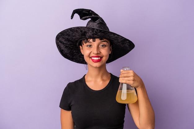 Giovane donna di razza mista travestita da strega che tiene pozione isolata su sfondo viola felice, sorridente e allegra.