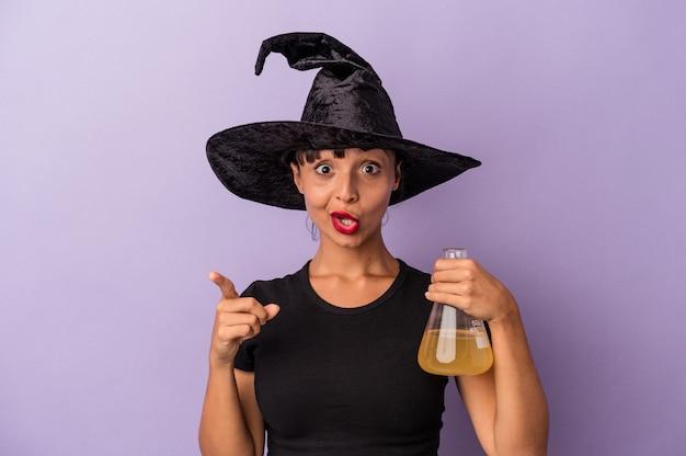 Giovane donna di razza mista travestita da strega che tiene pozione isolata su sfondo viola con un'idea, un concetto di ispirazione.