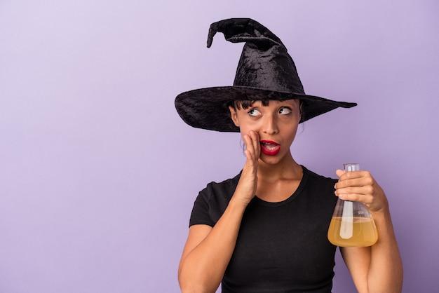 Giovane donna di razza mista travestita da strega che tiene pozione isolata su sfondo viola sta dicendo una notizia segreta di frenata calda e guardando da parte