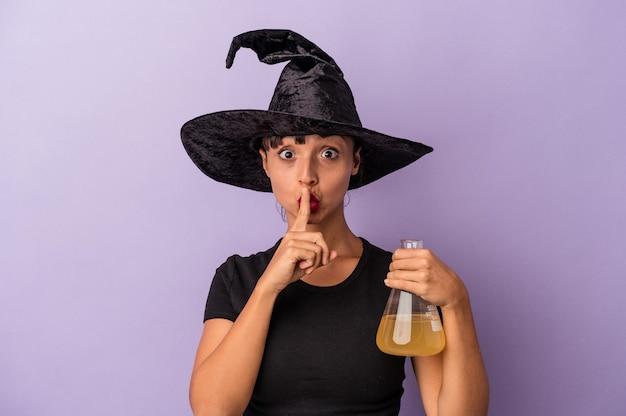 Giovane donna di razza mista travestita da strega che tiene pozione isolata su sfondo viola mantenendo un segreto o chiedendo silenzio.