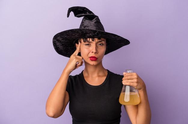 Giovane donna di razza mista travestita da strega che tiene pozione isolata su sfondo viola che punta il tempio con il dito, pensando, concentrata su un compito.