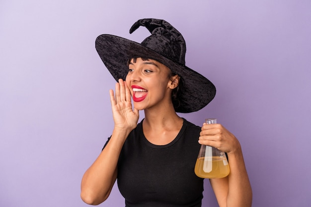 Giovane donna di razza mista travestita da strega che tiene pozione isolata su sfondo viola che grida e tiene il palmo vicino alla bocca aperta.