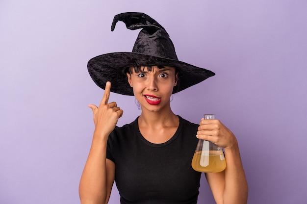 Giovane donna di razza mista travestita da strega che tiene pozione isolata su sfondo viola che mostra un gesto di delusione con l'indice.