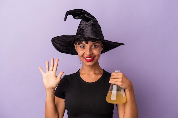 Giovane donna di razza mista travestita da strega che tiene pozione isolata su sfondo viola sorridente allegro che mostra il numero cinque con le dita.