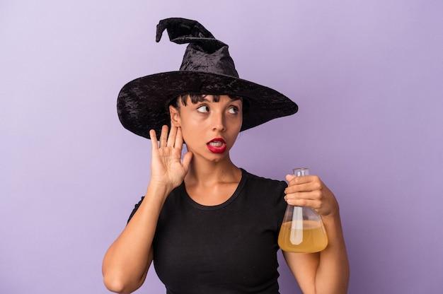 Giovane donna di razza mista travestita da strega che tiene pozione isolata su sfondo viola cercando di ascoltare un pettegolezzo.
