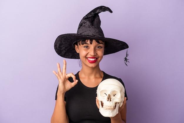 Giovane donna di razza mista travestita da strega che tiene in mano un teschio isolato su sfondo viola allegro e fiducioso che mostra gesto ok.