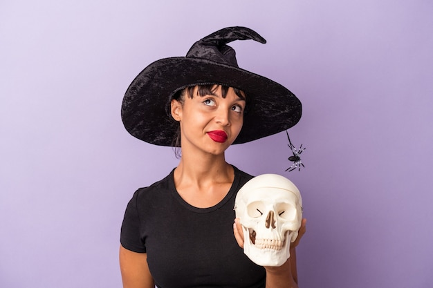 Giovane donna di razza mista travestita da strega che tiene un teschio isolato su sfondo viola che sogna di raggiungere obiettivi e scopi