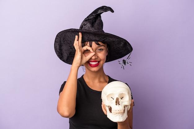 Giovane donna di razza mista travestita da strega che tiene in mano un teschio isolato su sfondo viola eccitato mantenendo il gesto ok sull'occhio.