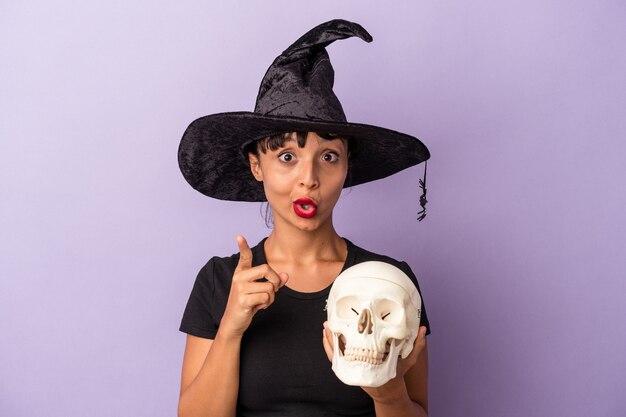 Giovane donna di razza mista travestita da strega che tiene in mano un teschio isolato su sfondo viola con un'idea, un concetto di ispirazione.