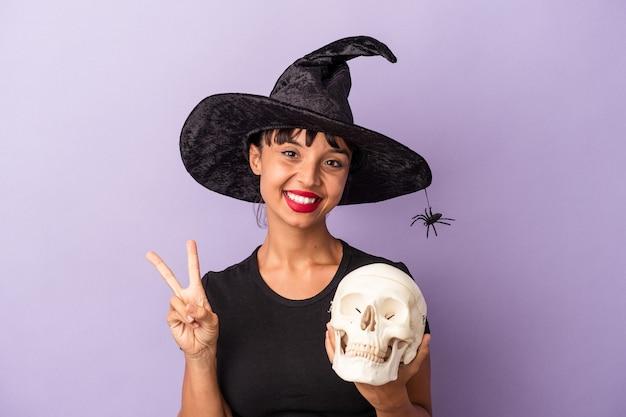 Giovane donna di razza mista travestita da strega che tiene un teschio isolato su sfondo viola gioiosa e spensierata che mostra un simbolo di pace con le dita.