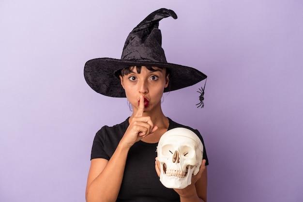 Giovane donna di razza mista travestita da strega che tiene in mano un teschio isolato su sfondo viola mantenendo un segreto o chiedendo silenzio.
