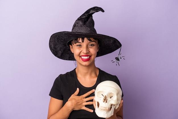 Giovane donna di razza mista travestita da strega che tiene in mano un teschio isolato su sfondo viola che ride e si diverte.