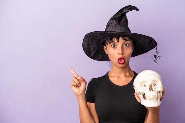 Giovane donna di razza mista travestita da strega che tiene in mano un teschio isolato su sfondo viola che punta al lato
