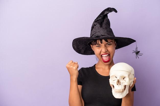 Giovane donna di razza mista travestita da strega che tiene un teschio isolato su sfondo viola che alza il pugno dopo una vittoria, concetto di vincitore.