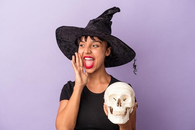 Giovane donna di razza mista travestita da strega che tiene in mano un teschio isolato su sfondo viola che grida e tiene il palmo vicino alla bocca aperta.