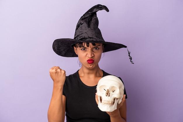Giovane donna di razza mista travestita da strega che tiene in mano un teschio isolato su sfondo viola che mostra il pugno alla telecamera, espressione facciale aggressiva.