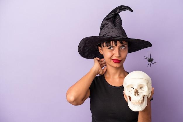 Giovane donna di razza mista travestita da strega che tiene in mano un teschio isolato su sfondo viola che tocca la nuca, pensa e fa una scelta.