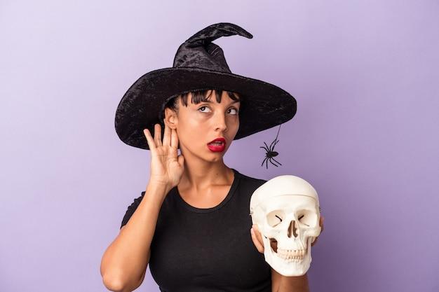 Giovane donna di razza mista travestita da strega che tiene un teschio isolato su sfondo viola cercando di ascoltare un pettegolezzo.
