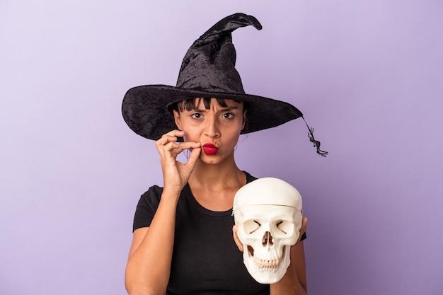 Giovane donna di razza mista travestita da strega che tiene in mano un teschio isolato su sfondo viola con le dita sulle labbra che tengono un segreto.