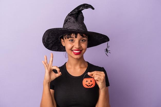 Giovane donna di razza mista travestita da strega isolata su sfondo viola allegro e fiducioso che mostra gesto ok.