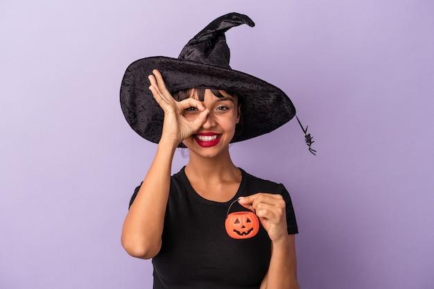 Giovane donna di razza mista travestita da strega isolata su sfondo viola eccitata mantenendo il gesto ok sull'occhio.