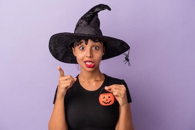 Giovane donna di razza mista travestita da strega isolata su sfondo viola con un'idea, un concetto di ispirazione.
