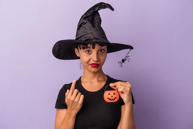 Giovane donna di razza mista travestita da strega isolata su sfondo viola che punta con il dito verso di te come se invitasse ad avvicinarsi.