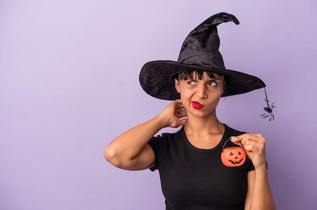 Giovane donna di razza mista travestita da strega isolata su sfondo viola toccando la parte posteriore della testa, pensando e facendo una scelta.