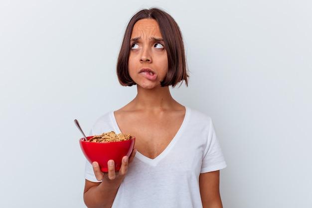 Giovane donna di razza mista che mangia cereali isolato sul muro bianco confuso, si sente dubbioso e insicuro.