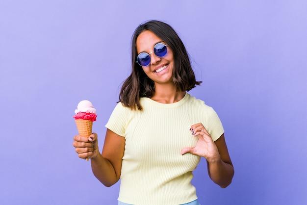 Giovane donna di razza mista che mangia un gelato sorridendo e mostrando una forma di cuore con le mani.