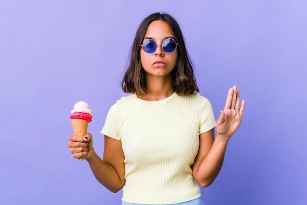 Giovane donna di razza mista che mangia un gelato in piedi con la mano tesa che mostra il segnale di stop, impedendoti.
