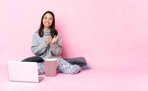 Giovane donna di razza mista che mangia popcorn mentre guarda un film sul portatile che applaude dopo la presentazione in una conferenza