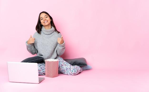 Giovane donna di razza mista che mangia popcorn mentre si guarda un film sul portatile dando un pollice in alto gesto