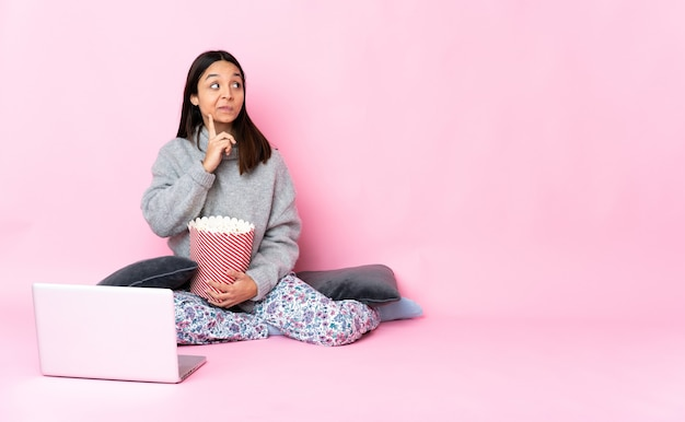 Giovane donna di razza mista che mangia popcorn mentre si guarda un film sul portatile avendo dubbi e pensando