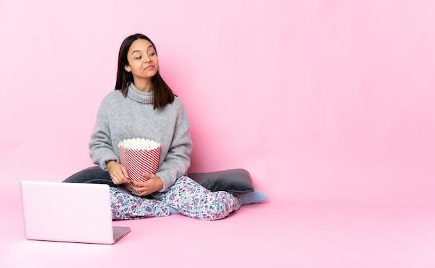 Giovane donna di razza mista che mangia popcorn mentre si guarda un film sul laptop che ha dubbi mentre si guarda di lato
