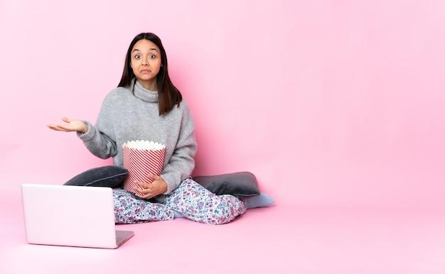 Giovane donna di razza mista che mangia popcorn mentre si guarda un film sul laptop che ha dubbi mentre si alzano le mani