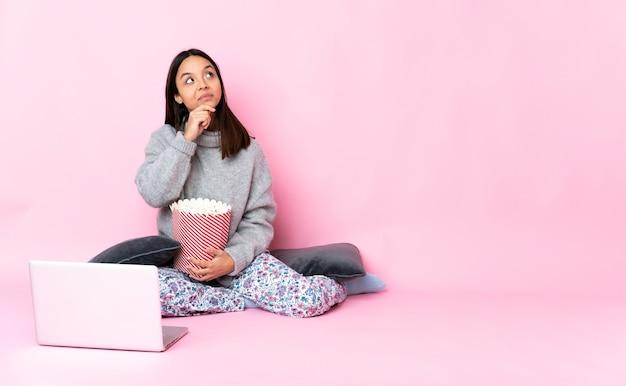 Giovane donna di razza mista che mangia popcorn mentre si guarda un film sul portatile avendo dubbi