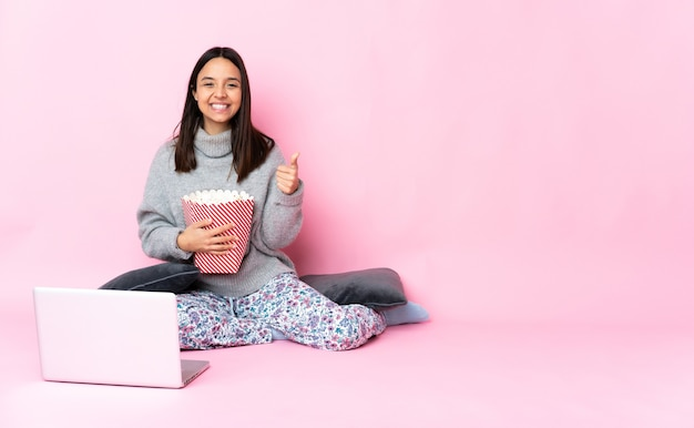Giovane donna di razza mista che mangia popcorn mentre guarda un film sul laptop tenendo un copyspace immaginario sul palmo per inserire un annuncio e con il pollice in alto