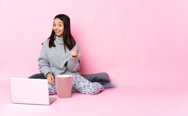 Giovane donna di razza mista che mangia popcorn mentre si guarda un film sul laptop che fa gesto di soldi