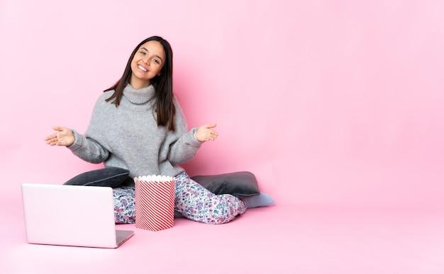 Giovane donna di razza mista che mangia popcorn mentre guarda un film sul laptop che presenta e invita a venire con la mano
