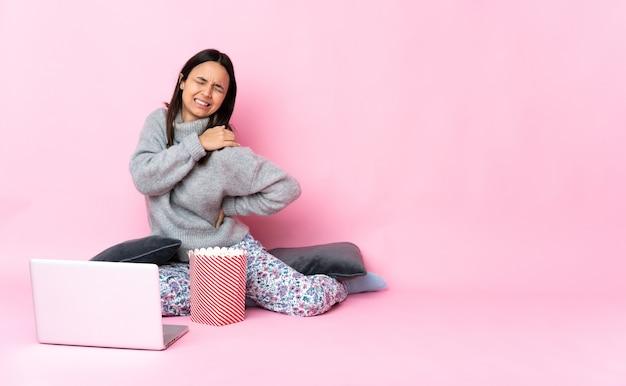 Giovane donna di razza mista che mangia popcorn mentre guarda un film sul laptop che soffre di dolore alla spalla per aver fatto uno sforzo