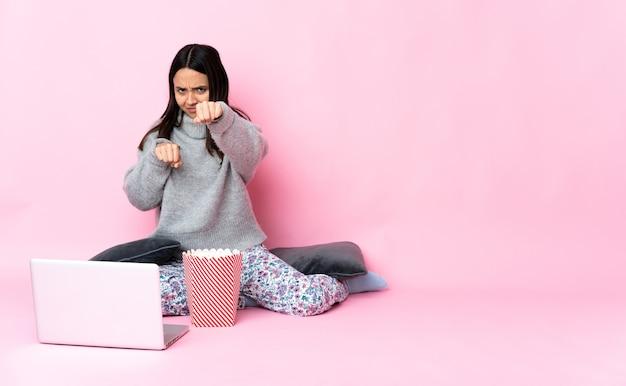 Giovane donna di razza mista che mangia popcorn mentre si guarda un film sul laptop con gesto di combattimento