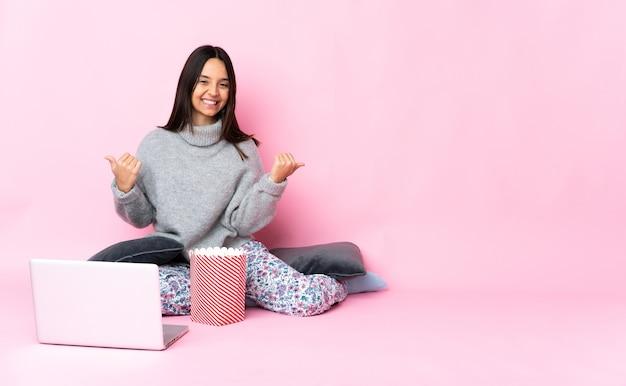 Giovane donna di razza mista che mangia popcorn mentre guarda un film sul portatile con il gesto del pollice in alto e sorridente