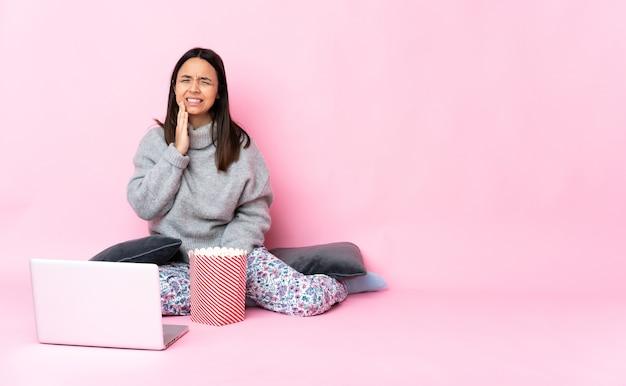 Giovane donna di razza mista che mangia popcorn mentre si guarda un film sul laptop con mal di denti