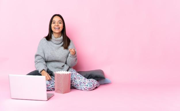 Giovane donna di razza mista che mangia popcorn mentre si guarda un film sul computer portatile