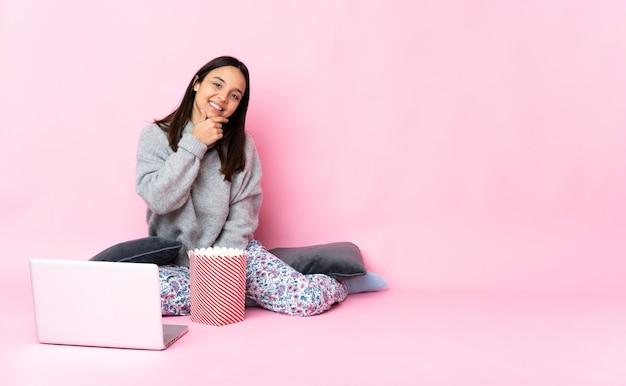 Giovane donna di razza mista che mangia popcorn mentre guarda un film