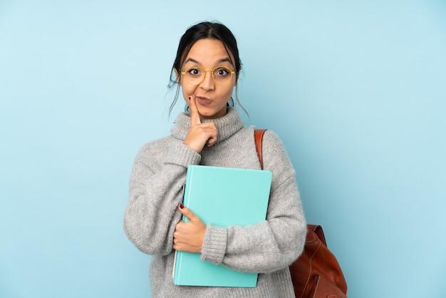 Giovane donna della corsa mista che va a scuola sulla parete blu e che sembra anteriore