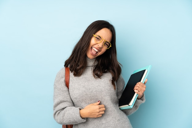 Giovane donna di razza mista che va a scuola isolata sulla parete blu che fa il gesto della chitarra