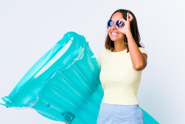 Giovane donna di razza mista che tiene un materasso ad aria eccitato mantenendo il gesto ok sull'occhio.